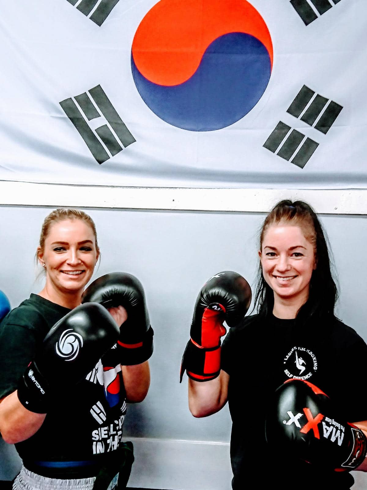 Two female kickboxing students posing wearing boxing gloves