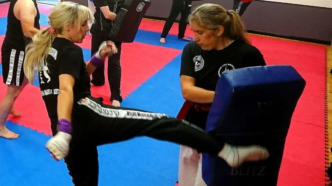 Female self-defence student kicking student holding pad