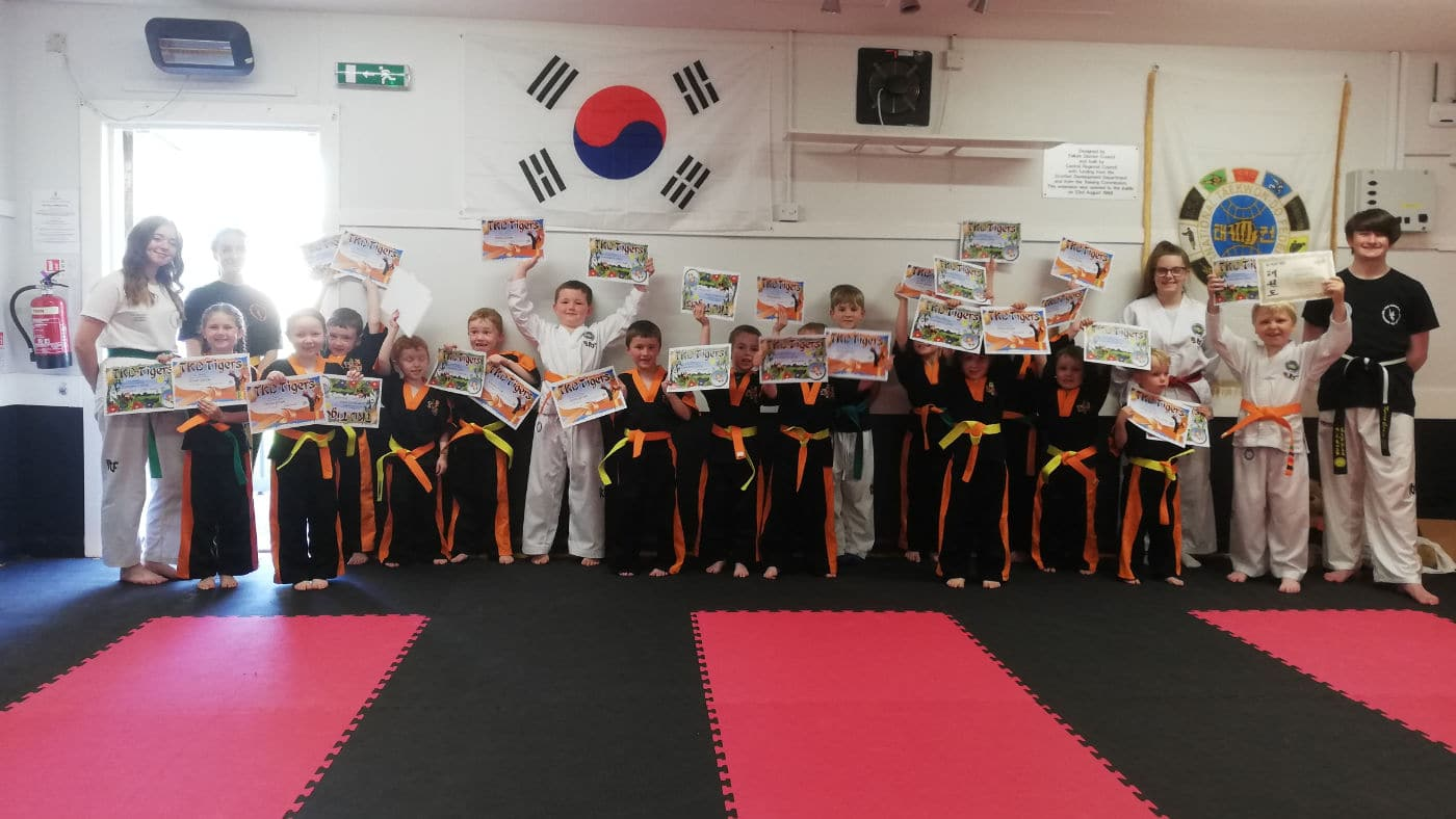 Young taekwon-do students proudly posing for group photo