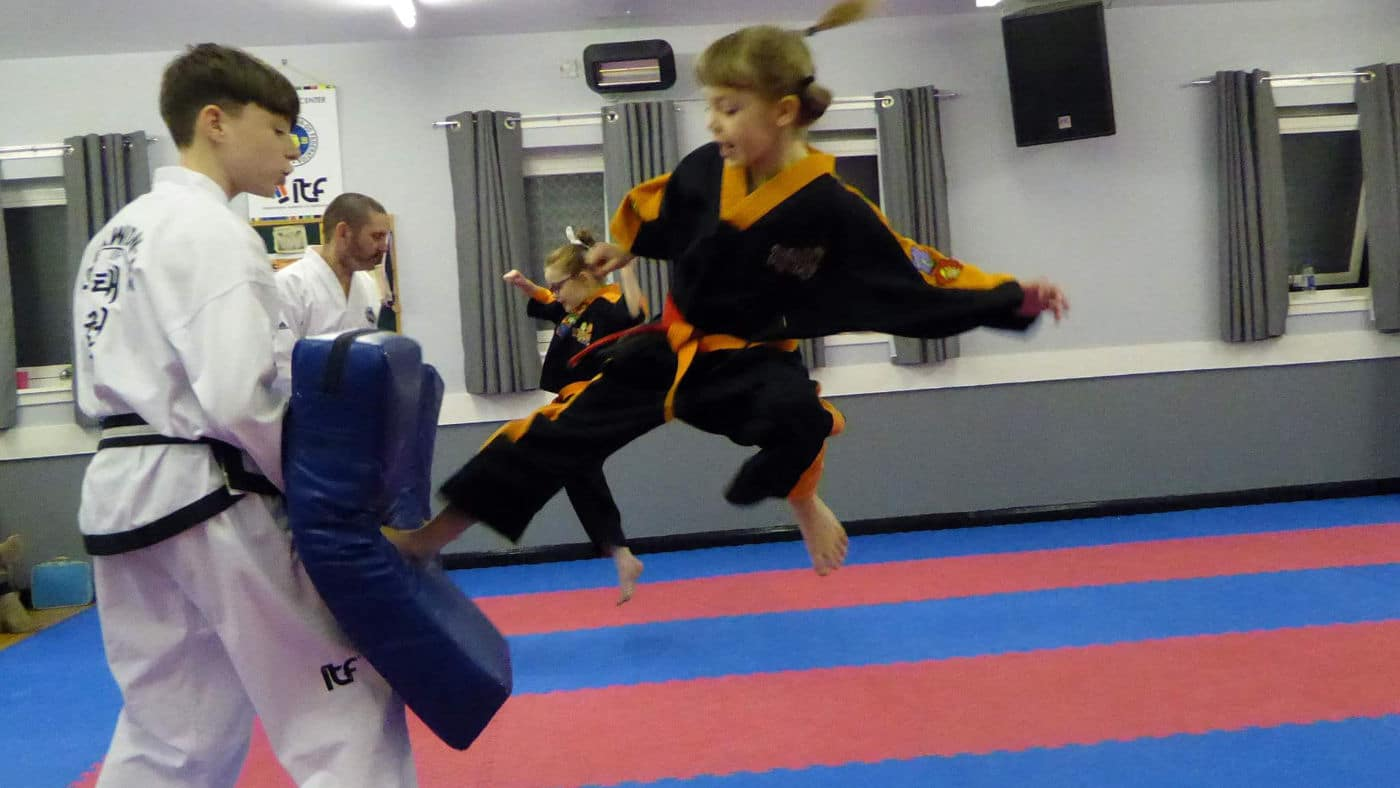 Young taekwon-do student fly kicking student holding pad