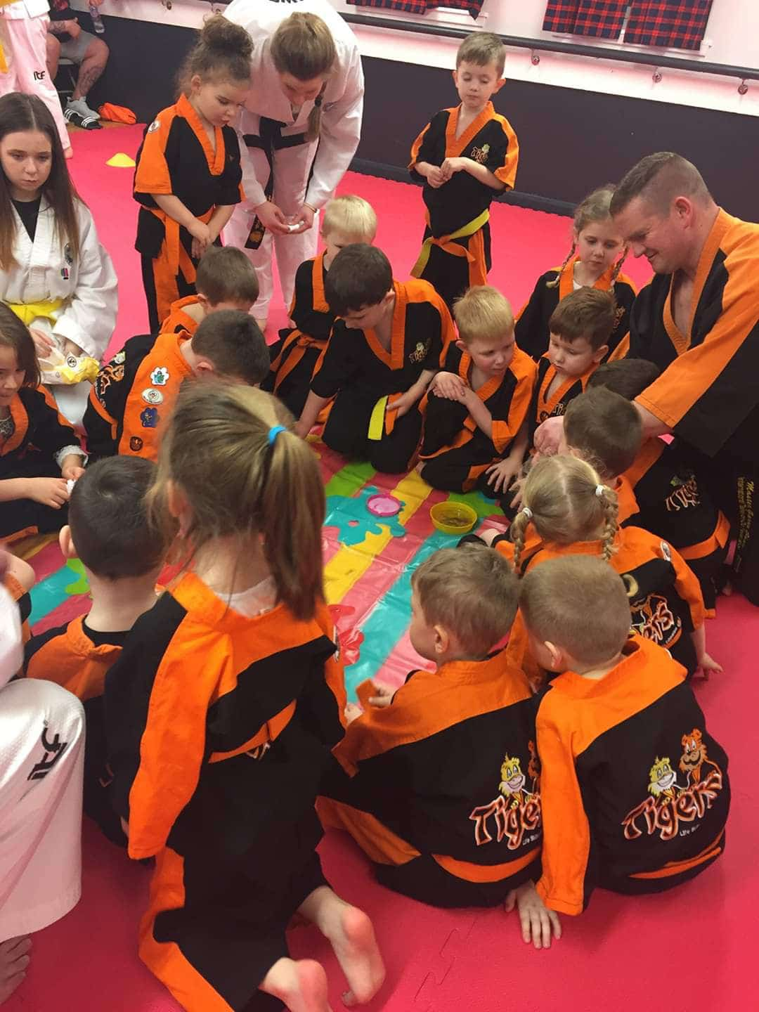 Young taekwon-do students taking a break to enjoy playing a game with their master
