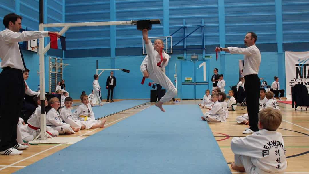 Taekwon-Do student performing high kick in competition